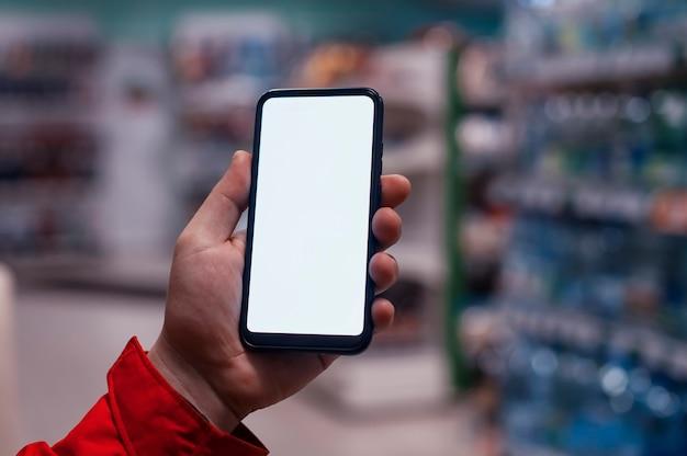 Makieta smartfona z białym ekranem w rękach mężczyzny. telefon na przestrzeni gablot w sklepie.