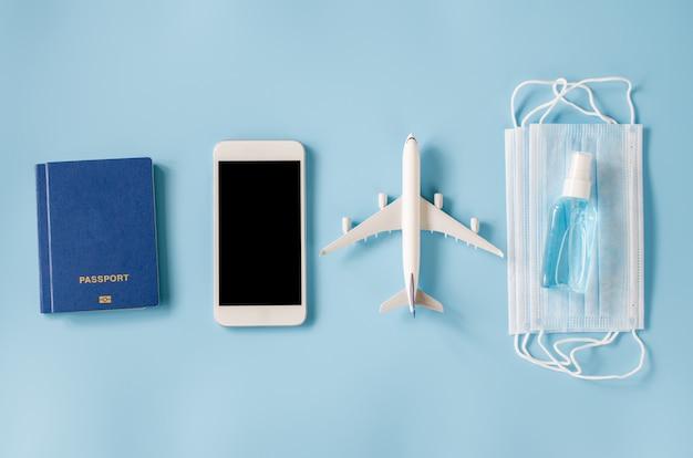 Makieta smartfona z modelem samolotu, paszportami, maską i środkiem dezynfekującym do rąk