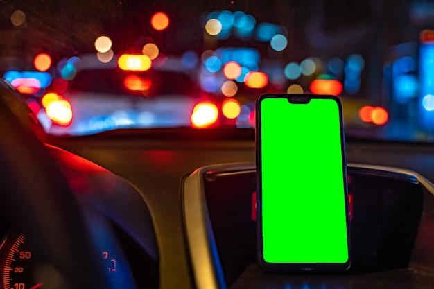 Makieta smartfona z zielonym ekranem w samochodzie podczas jazdy, aby dodać gps lub aplikację