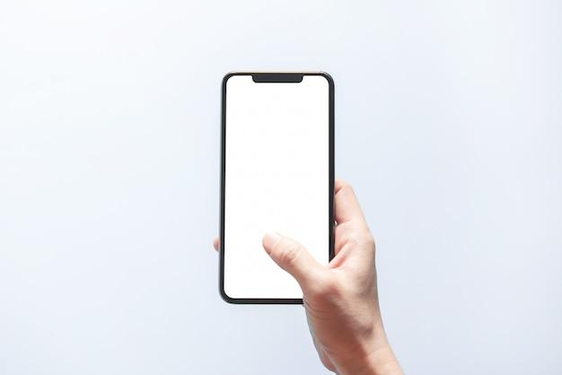 Makieta smartfona. zamyka w górę ręki trzyma czarnego telefonu bielu ekran. pojedynczo na białym tle. koncepcja bezramowego telefonu komórkowego.