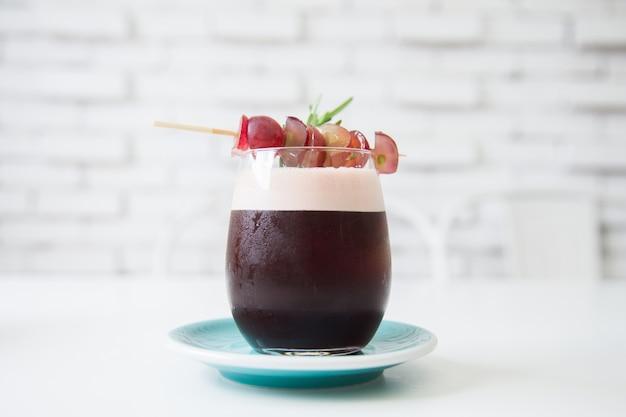 Makieta sody winogronowej ze świeżymi winogronami. miękka ostrość świeżego drinka w vintage kawiarni. tradycyjny letni napój