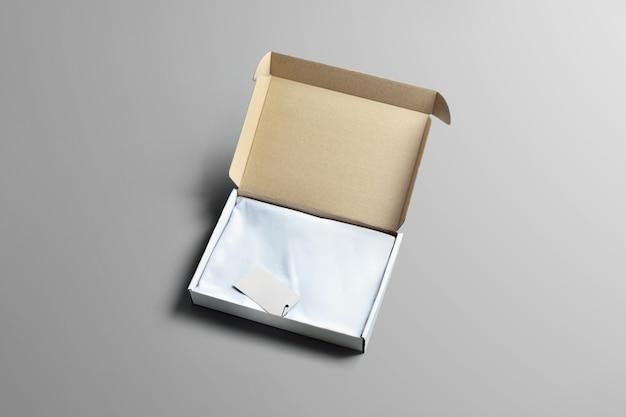 Makieta studyjna kartonu na ubrania. otwarty karton z pustą koszulką na szarym tle. szablon może służyć do prezentacji.