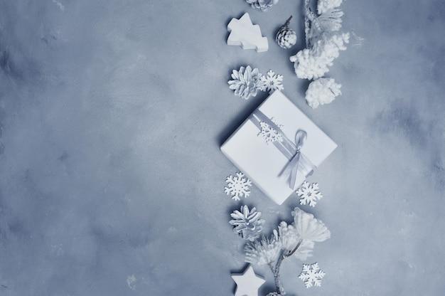 Makieta świąteczna ramka ze stożkami, płatkiem śniegu i drewnianymi zabawkami oraz obramowaniem pudełek na prezenty.
