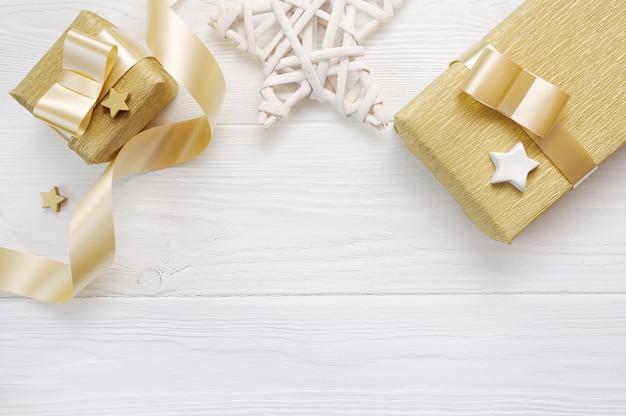 Makieta świątecznej gwiazdy i złota wstążka prezentowa, flatlay na białym