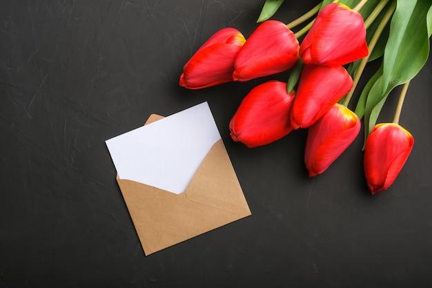 Makieta świeży czerwony tulipan bukiet i pustą kartkę z życzeniami w kopercie kraft