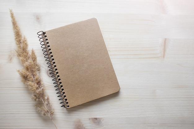 Makieta szablon z czarną pustą okładką notatnika na drewnianym