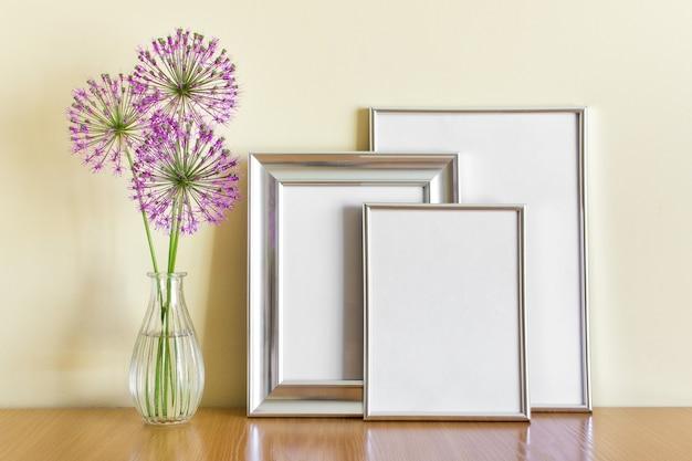 Makieta szablon ze stojącym stosem srebrnych ramek i różowymi okrągłymi letnimi kwiatami czosnku w szklanym wazonie.