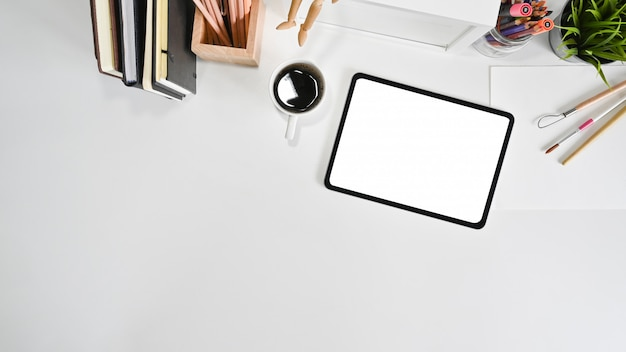 Makieta tablet, kawa i materiały biurowe na białym biurku z widokiem z góry.