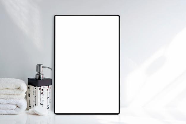 Makieta tablet z pustym białym ekranem i ręcznikiem kąpielowym z mydłem na białym stole w białym pokoju,