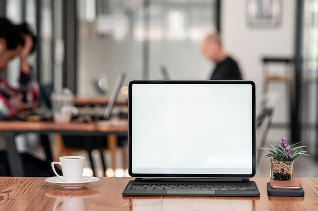 Makieta tablet z pustym ekranem z klawiaturą na drewnianym stole w kawiarni.
