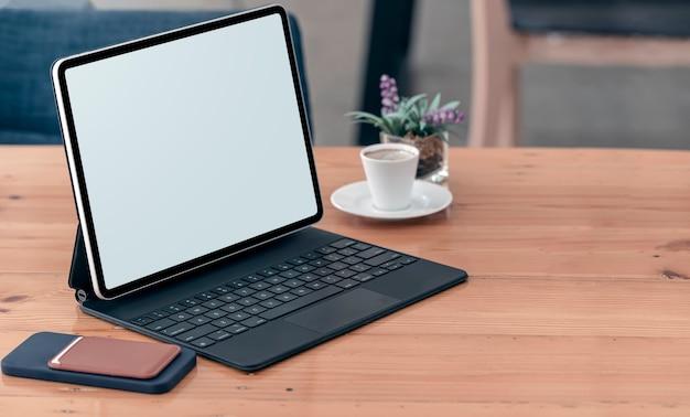 Makieta tablet z pustym ekranem z klawiaturą na drewnianym stole.