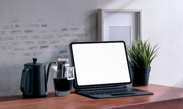 Makieta tablet z pustym ekranem z magiczną klawiaturą i kroplową kawą na drewnianym stole.