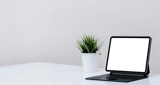 Makieta tablet z pustym ekranem z magiczną klawiaturą na białym stole w białym pokoju, miejsce.