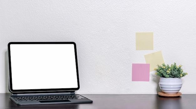 Makieta tablet z pustym ekranem z magiczną klawiaturą na czarnym drewnianym stole i białej ścianie