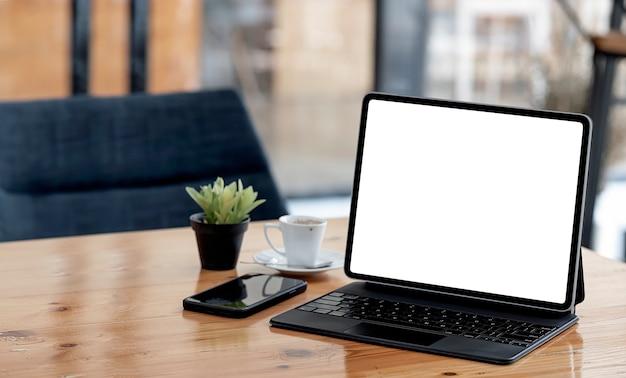 Makieta tablet z pustym ekranem z magiczną klawiaturą na drewnianym stole w kawiarni.