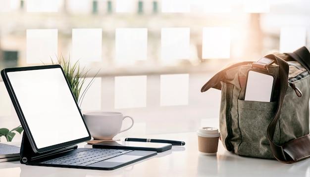 Makieta tabletu z pustym ekranem na stole i smartfon z pustym ekranem w torbie na ramię.