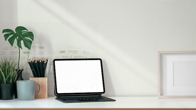 Makieta tabletu z pustym ekranem z magiczną klawiaturą i materiałami na drewnianym stole.