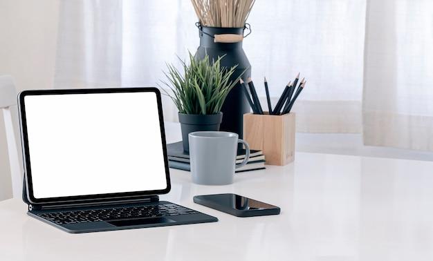 Makieta tabletu z pustym ekranem z magiczną klawiaturą na białym stole w salonie.