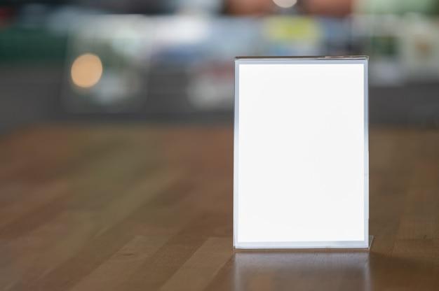 Makieta tablica reklamowa pusty biały ekran na drewnianym stole z rozmytym tłem