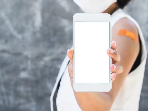 Makieta telefonu, biały pusty ekran na smartfonie trzyma i pokazuje przez zaszczepioną kobietę, która ma na sobie białą marynarkę bez rękawów, maskę na twarz i bandaż na ramieniu z miejscem na kopię.