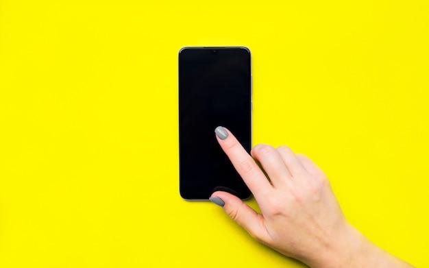 Makieta telefonu. dziewczyna przewraca strony. przesuń palcem po ekranie. żółte tło. piękny manicure. leżał na płasko. kolor roku 2021.