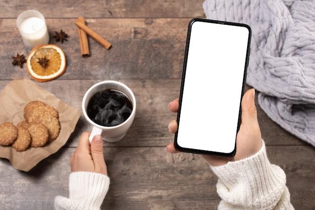 Makieta telefonu komórkowego. kobieta przy drewnianym stole w stylu rustykalnym pije kawę i patrzy na makietę telefonu komórkowego