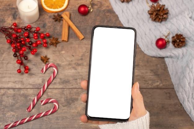 Makieta telefonu komórkowego na tle drewnianym stole podczas świąt bożego narodzenia.