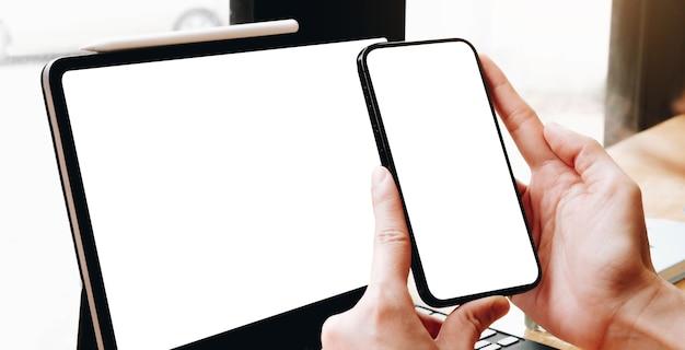 Makieta telefonu komórkowego. ręka kobieta pracuje za pomocą laptopa sms-y na telefon komórkowy. pusty ekran z białym tłem dla reklamy