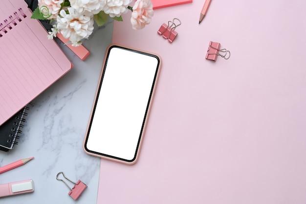 Makieta telefonu komórkowego z pustym ekranem na różowym i marmurowym tle.