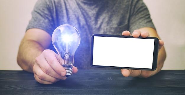 Makieta telefonu . mężczyzna trzymający telefon z białym ekranem i żarówką, inwestycja w pomysły, inwestycja w startup.