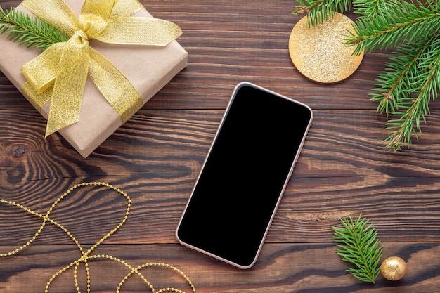 Makieta telefonu z czarnym ekranem i prezentem świątecznym