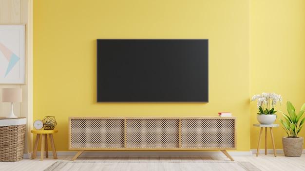 Makieta telewizora zamontowanego na ścianie w salonie z żółtą ścianą