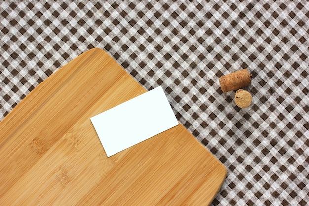Makieta, twórca scen. jedna pusta wizytówka, korki do wina i bambusowa deska do krojenia na obrusie w kratkę, widok z góry. stół kuchenny. skopiuj miejsce.