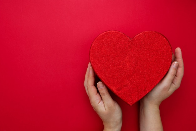 Makieta walentynek. kobieta wręcza mienia serca pudełko na czerwonym tle z kopii przestrzenią. streszczenie czerwone pudełko.