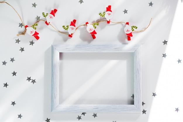 Makieta wesołych świąt i nowego roku. bożenarodzeniowy santa, srebro gwiazda i biel rama na bielu. makieta flatlay