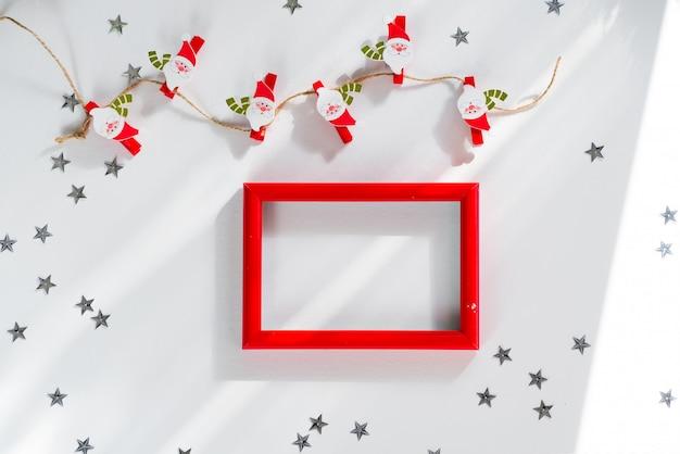 Makieta wesołych świąt i nowego roku. bożenarodzeniowy santa, srebro gwiazda i czerwieni rama na bielu. makieta flatlay