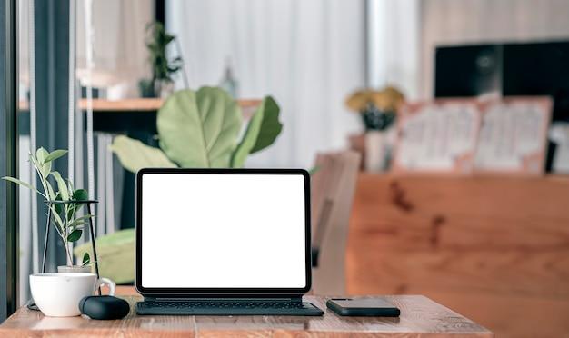 Makieta wygodnego miejsca do pracy z komputerem typu tablet z pustym ekranem na drewnianym stole w kawiarni.