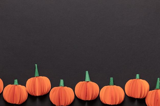 Makieta z halloween. czarne tło ramki z nietoperzami wyciętymi z papieru, dynią i duchem.