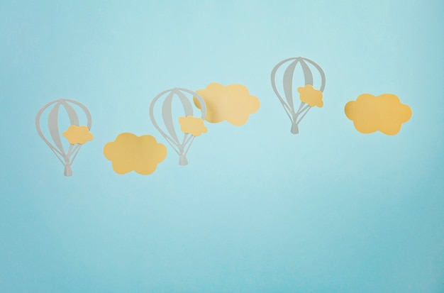 Makieta z papierowymi chmurami i latającymi balonami na niebieskim pastelowym tle