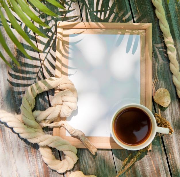 Makieta z pustą drewnianą ramą, liną i filiżanką kawy, letnie zdjęcie na zewnątrz