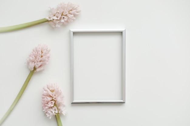 Makieta z różowymi kwiatami i pustą ramką na zdjęcia z miejscem na kopię.