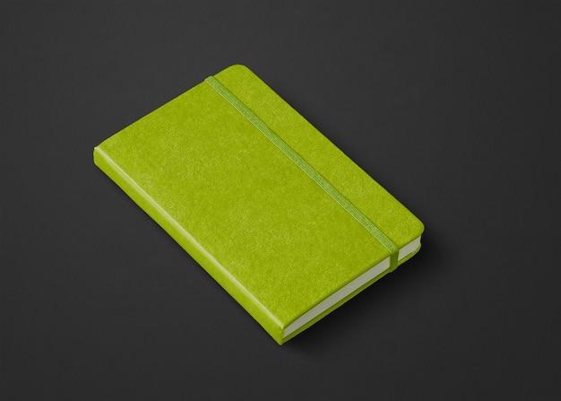 Makieta zamkniętego notebooka w kolorze limonki na czarnym tle