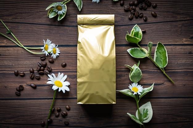Makieta złotej metalicznej torebki papierowej na ciemnym drewnianym stole leżącym w ziarnach kawy