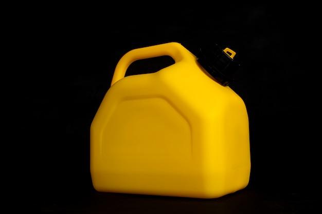 Makieta żółtego plastikowego kanistra na paliwo samochodowe na czarnym tle. pojemnik na płyny i paliwa niebezpieczne.