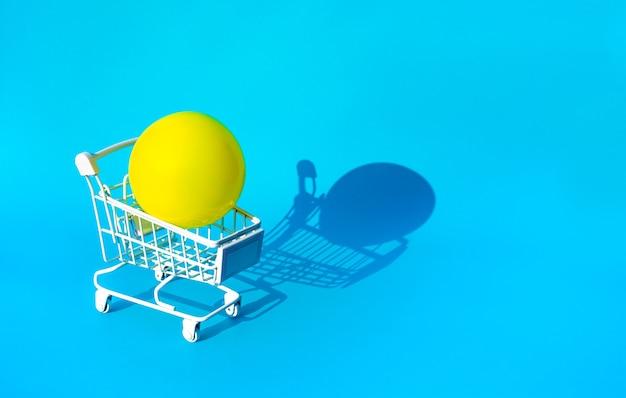 Makieta żółtej piłki na carttrolley dla koncepcji zakupów w supermarkecie