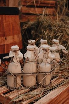 Makiety butelek po mleku na sianie jesienne targi wiejskie styl rustykalny naturalne produkty święto dziękczynienia