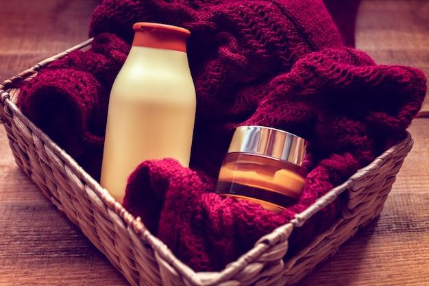 Makiety butelek z kremem do ciała i szamponem na swetrze
