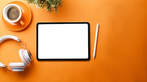 Makiety cyfrowy stół z pustym ekranem, filiżanką kawy i słuchawkami na pomarańczowym tle.