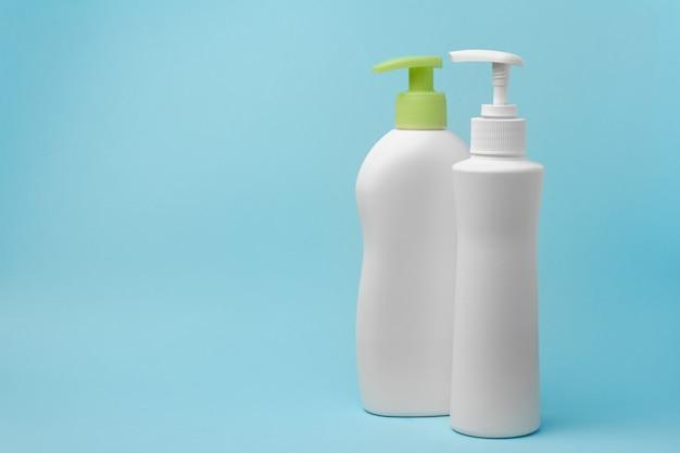 Makiety dwóch białych butelek z dozownikiem mydła w płynie znajdują się na niebieskim tle podłoża. roztwór dezynfekujący przeciwko covid-19