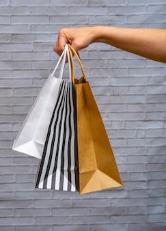 Makiety eko opakowania zbliżenie na szarym tle cegły. torba kraft w czarno-białe paski, biała, rzemieślnicza w kobiecej dłoni. koncepcja zakupów online, dostawa, zamówienia online.